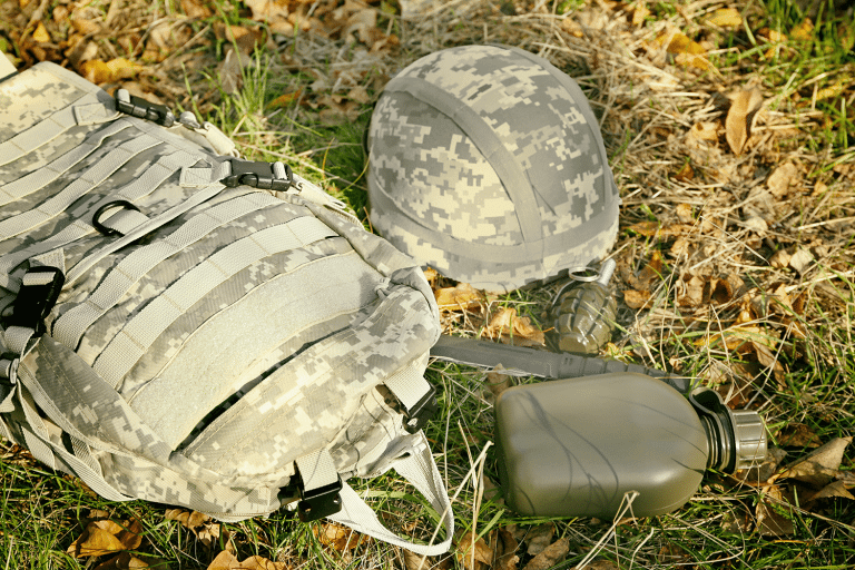 tactical backpack and helmet on grass
