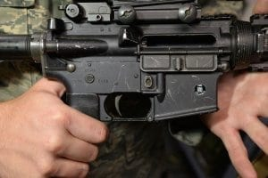 Man in camo holding a firearm closeup
