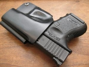 Black plastic weapon holster with gun inside