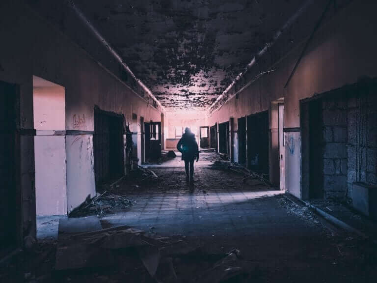 Person walking down hallway and destroyed building